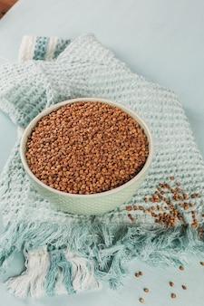 Ciotola di semole di grano saraceno crudo secco su superficie azzurra. cucinare il concetto di porridge di grano saraceno.