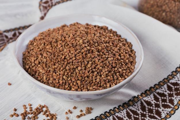 Ciotola di semole di grano saraceno crudo secco su un fondo di legno bianco. cucinare il concetto di porridge di grano saraceno.