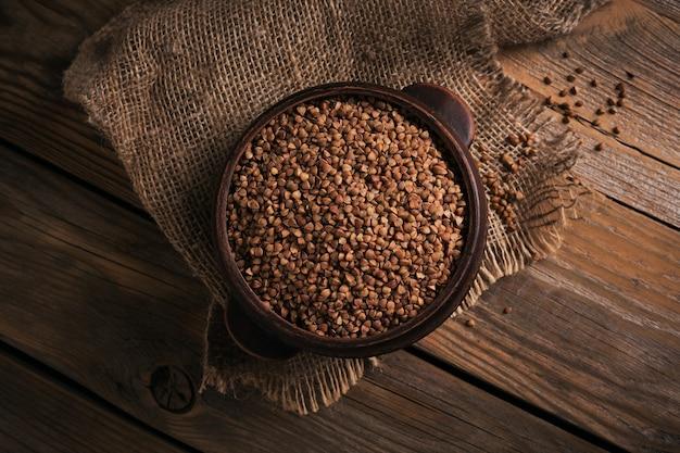 Ciotola di semole di grano saraceno crudo secco su un legno