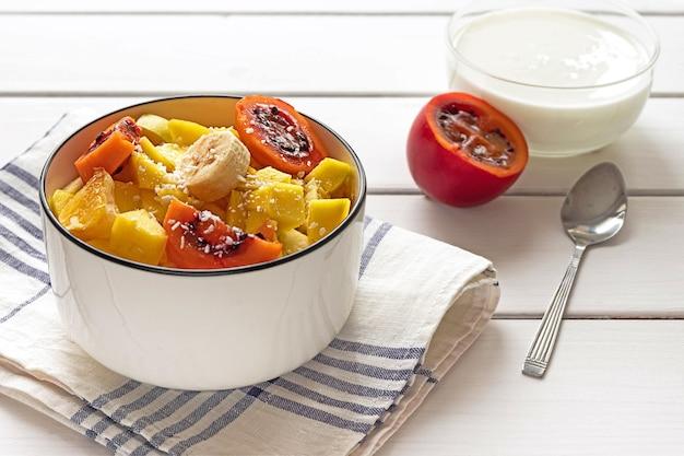 Ciotola di macedonia di frutta fresca con scaglie di cocco, tamarillo tagliato e yogurt in background