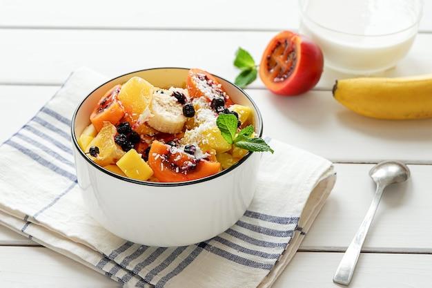Ciotola di insalata di frutta fresca con scaglie di cocco e yogurt in background