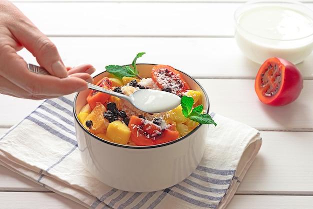 Ciotola di insalata di frutta fresca, con tamarillo tagliato e yogurt in background