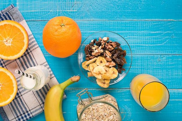Ciotola di porridge di farina d'avena fresca con banana e noci su tavola rustica verde acqua, cibo caldo e sano per la colazione. vista dall'alto. copia spazio