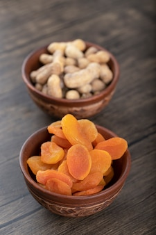 Ciotola piena di sane albicocche secche frutta e arachidi posto su un tavolo di legno.