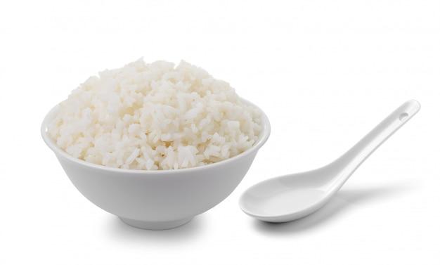 Ciotola in pieno di riso e di cucchiaio isolati