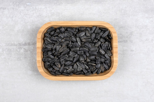 Ciotola piena di semi di girasole neri posti sulla pietra.