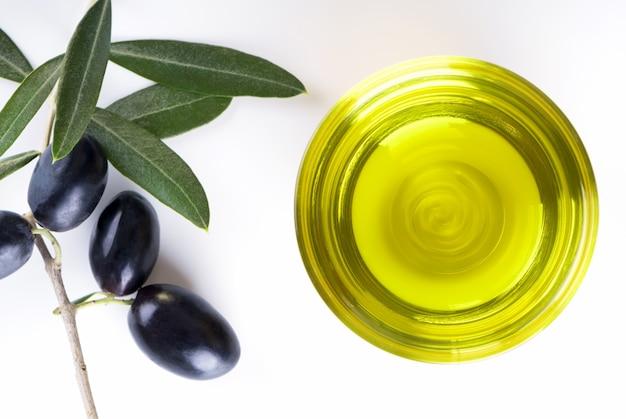 Ciotola di vetro piena di olio extra vergine di oliva su un tavolo bianco con ramo d'ulivo