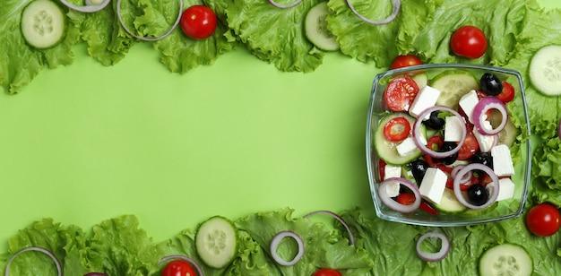 Ciotola di insalata greca e ingredienti sulla superficie verde