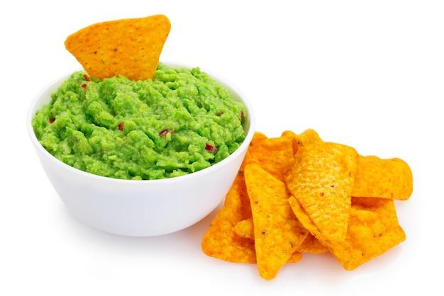 Ciotola di guacamole con nachos isolato su sfondo bianco