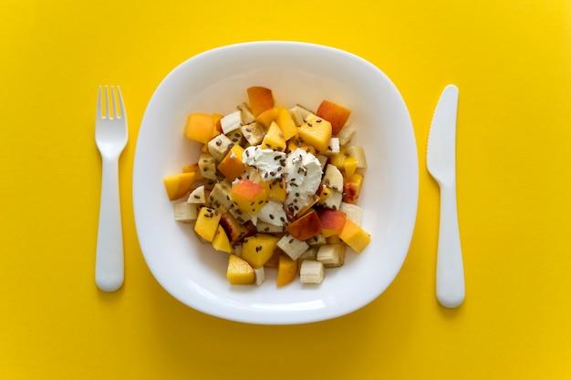 Ciotola di sana insalata di frutta fresca su giallo. insalata di frutta sana nutrizione con formaggio a pasta molle e semi di lino nel piatto bianco su sfondo giallo con coltello e forchetta bianchi.
