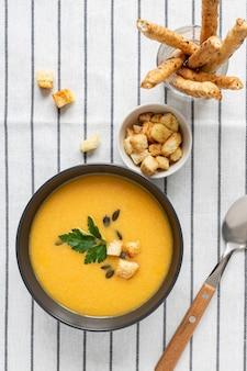 Una ciotola di zuppa di zucca cremosa organica piccante fresca fatta in casa su uno sfondo bianco a strisce tessili con grissini, panna acida, prezzemolo e spezie.