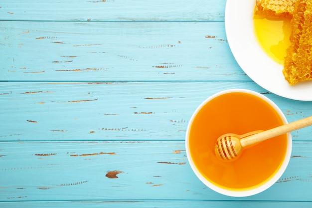 Ciotola di miele con il favo sulla tavola di legno blu