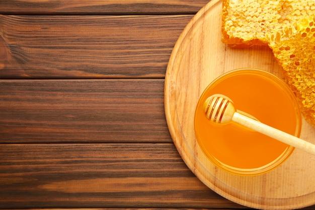 Ciotola di miele con il favo sulla tavola di legno marrone