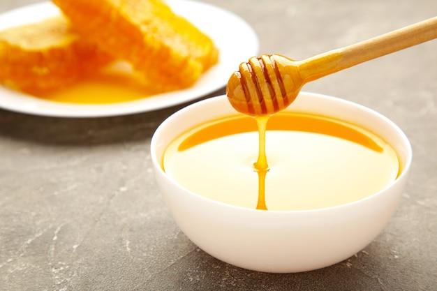 Ciotola di miele con favo sul tavolo grigio. vista dall'alto