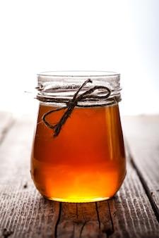 Ciotola di miele sulla tavola di legno. simbolo di una vita sana e medicina naturale.