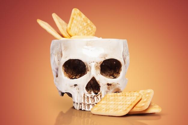 Ciotola di un teschio umano con salsa di formaggio e cracker di ioni di colore sfondo