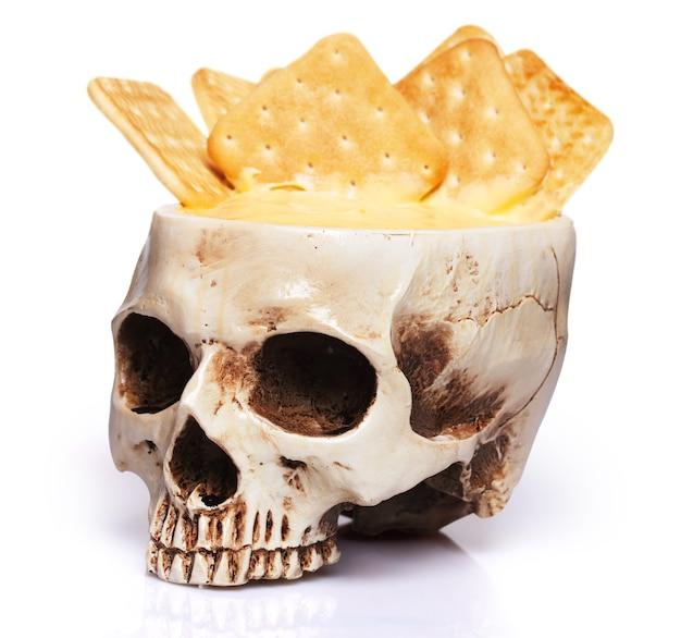 Ciotola di un teschio umano con salsa di formaggio e cracker isolati su sfondo bianco