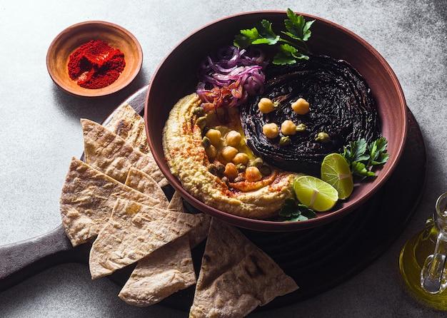 Una ciotola di hummus, cavolo viola al forno e cipolla rossa in salamoia con una tortilla e paprika affumicata