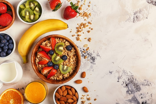Ciotola di muesli, bacche e frutta, noci, succo d'arancia, latte