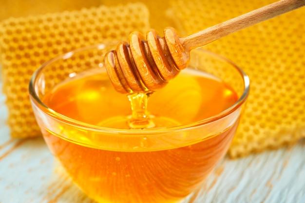 Ciotola miele naturale sul tavolo rustico blu, con nido d'ape, primo piano.