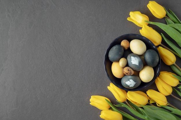 Ciotola di uova di pasqua tinte naturalmente e fiori gialli sul tavolo grigio, spazio libero.