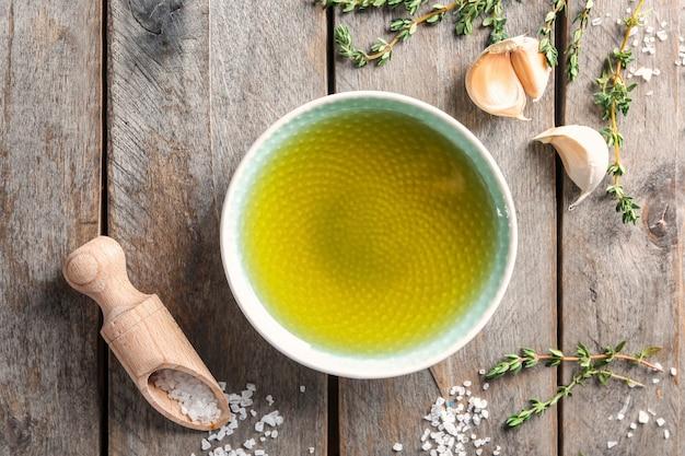 Ciotola di olio d'oliva, aglio e cucchiaio con sale su fondo in legno, vista dall'alto