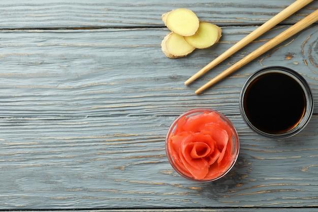 Ciotola di zenzero sottaceto, salsa di soia e bacchette sulla tavola di legno