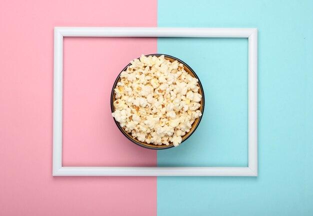 Ciotola di popcorn sulla superficie pastello blu rosa con cornice bianca