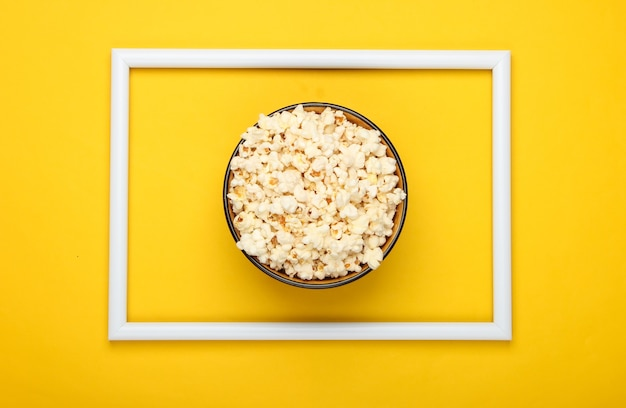 Ciotola di popcorn sulla superficie gialla con cornice bianca