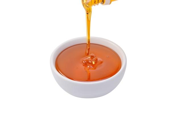 Ciotola di miele versando isolato su sfondo bianco