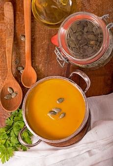 Ciotola di zuppa di zucca su fondo di legno rustico.