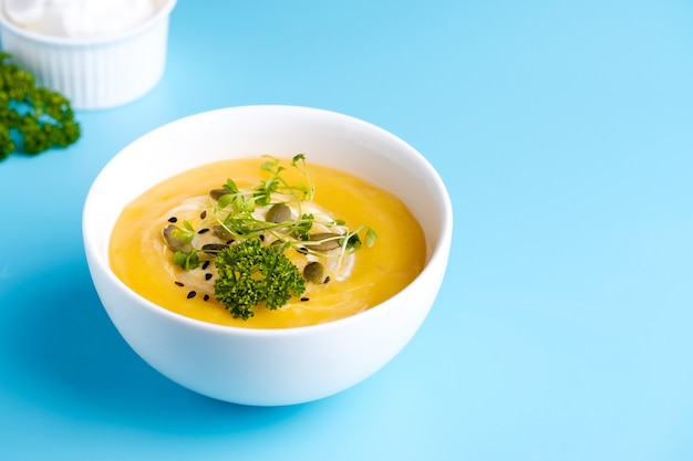 Ciotola di zuppa di zucca con foglia verde. vista dall'alto