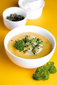 Ciotola di zuppa di zucca con foglia verde