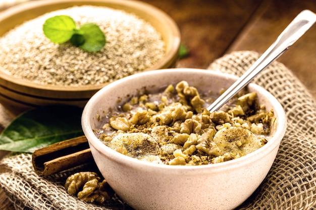 Ciotola di porridge di quinoa, con banana, noci e cannella. dessert vegano senza lattosio, dolce senza latte