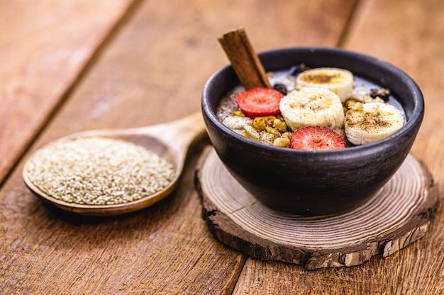 Ciotola di porridge di quinoa con banana, noci e cannella. colazione vegana, con cucchiaio sul fondo di chicchi di quinoa