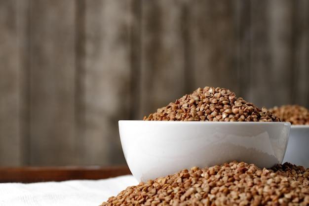 Ciotola di grano saraceno crudo crudo sulla tavola di legno
