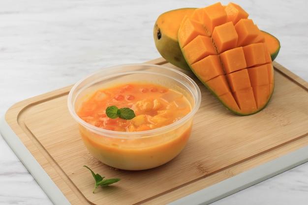 Una ciotola di mango sagoo (mango lolo) o budino di mango, dessert di mango di hong kong a base di succo di mango, gelatina e perla di sago/tapioca. servito freddo.