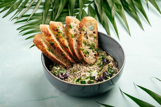Ciotola di hummus salato con pane tostato