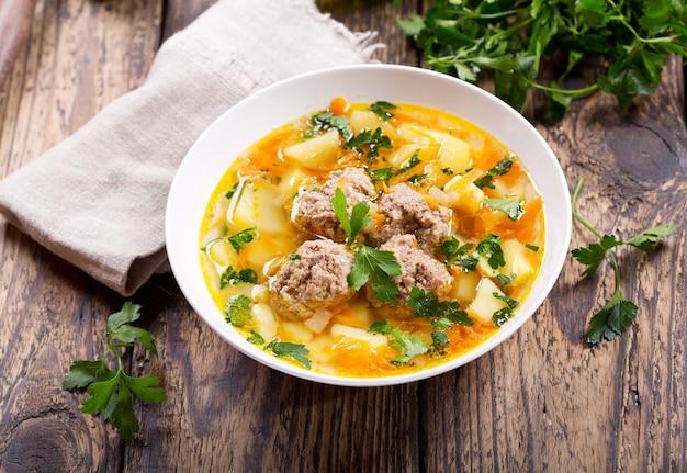 Ciotola di zuppa con polpette di carne e verdure sulla tavola di legno