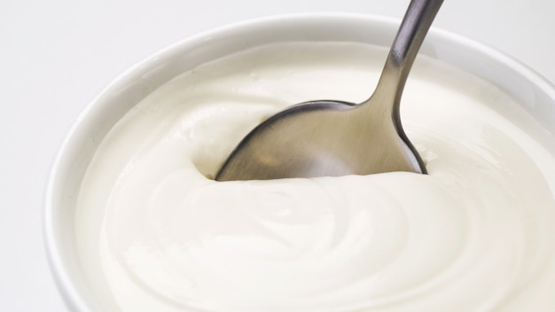 Ciotola di panna acida, yogurt greco con cucchiaio, macro