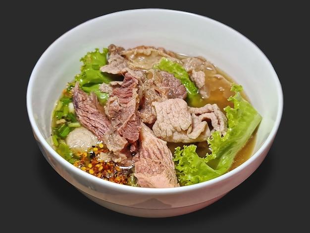 Una ciotola di zuppa piccante con manzo e polpette isolate su gray
