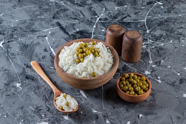 Ciotola di riso bianco al vapore con piselli su sfondo marmo.