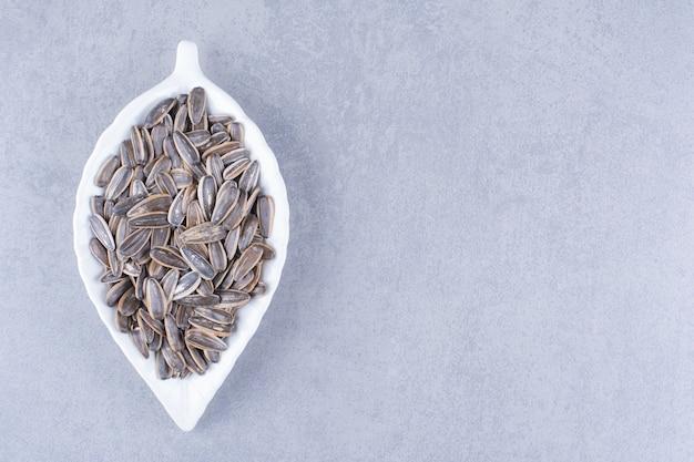Una ciotola di semi di girasole sulla superficie del marmo