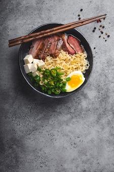 Ciotola di gustosa zuppa di noodle asiatici ramen con brodo, tofu, maiale, uova su fondo di cemento rustico grigio, spazio per il testo, primo piano, vista dall'alto. zuppa calda e gustosa di ramen giapponese per cena con spazio per le copie