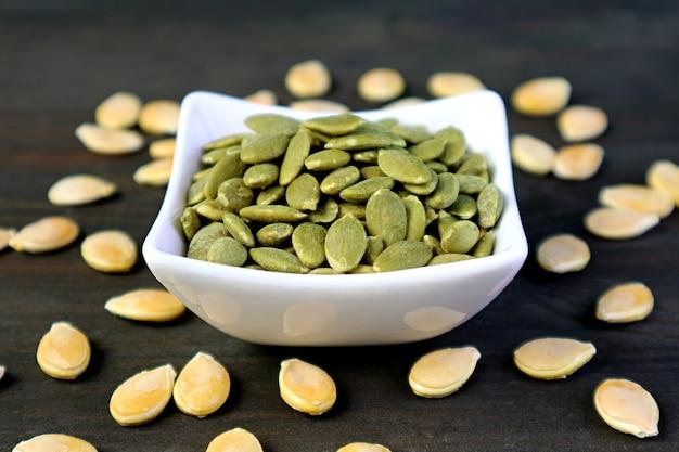 Ciotola di semi di zucca arrostiti gustosi e sani con semi crudi sparsi sul tavolo di legno