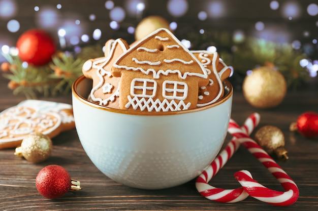 Ciotola di gustosi biscotti fatti in casa di natale, caramelle, giocattoli su legno, spazio per il testo. avvicinamento