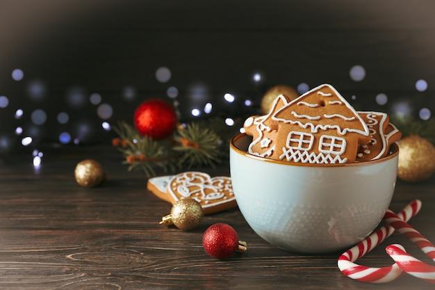 Ciotola di gustosi biscotti fatti in casa di natale, caramelle, giocattoli su legno, spazio per il testo