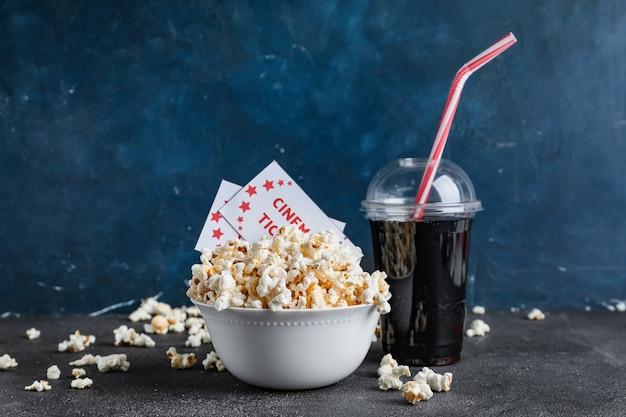 Ciotola di gustosi popcorn con biglietti del cinema e cola su sfondo scuro