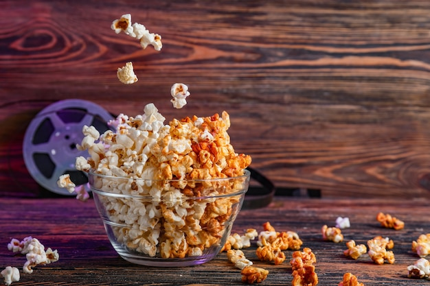 Ciotola di gustosi popcorn su sfondo di legno