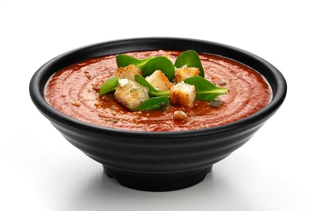 Ciotola di zuppa di pomodoro in ciotola nera isolata su sfondo bianco white